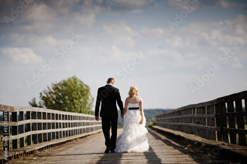 Married couple walking across the bridge