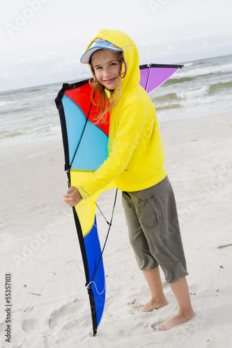 Fun on the beach - young girl playing with kite