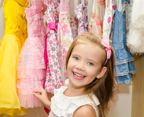 Smiling little girl chooses a dress from the wardrobe