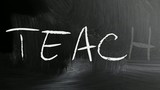 """Teach"" handwritten with white chalk on a blackboard."
