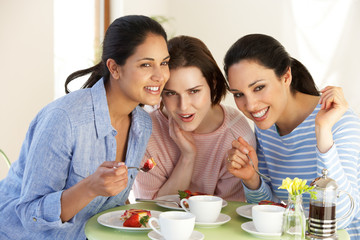 Three Women Having Snack In Cafe