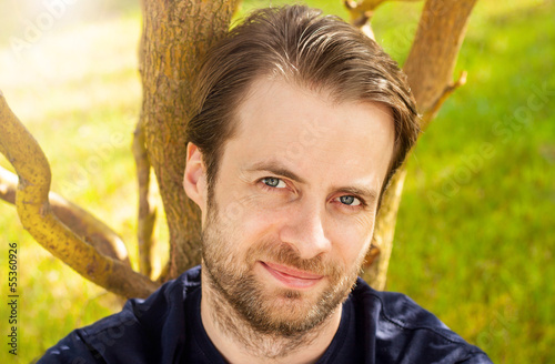 Portrait of happy man sitting by a tree outdoor in the garden
