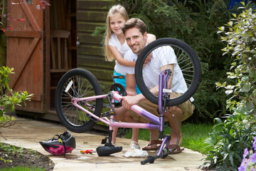 Father And Daughter Mending Bike Together
