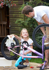 Father And Daughter Cleaning Bike Together