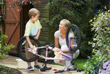 Mother And Son Cleaning Bike Together