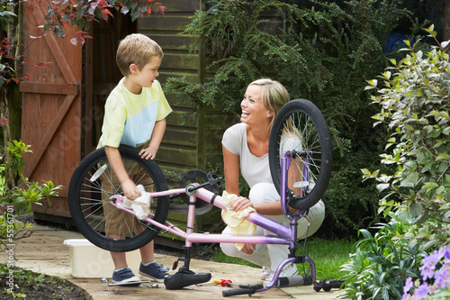 Mother And Son Cleaning Bike Together - 55361701