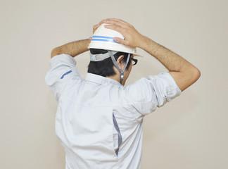 頭を抱え込む男性作業員