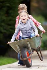 Boy Giving Girl Ride In Wheelbarrow