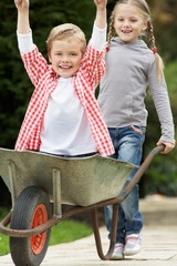Girl Giving Boy Ride In Wheelbarrow