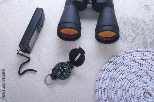 bussola e binocoli e fune e GPS su carta nautica