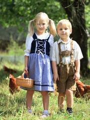 Kinder in Tracht beim Eier sammeln
