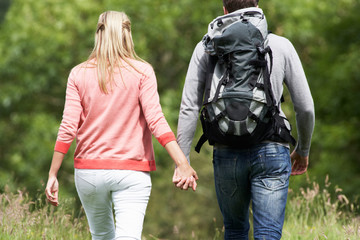Rear View Of Couple Hiking In Countryside