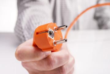 Hand hält den Stecker eines Elektrogerätes