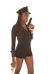 Cop woman with gun and cuffs side serious