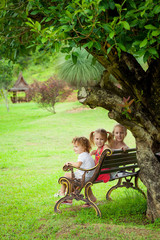 happy kids sitting on the bench near the tree