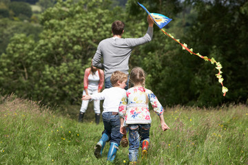 Rear View Of Family Flying Kite In Countryside
