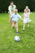 Family Playing Football In Garden