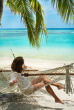 Girl in a hammock on the shores of the azure ocean (Maldives - L