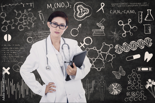 Confident female doctor hold e-tablet on written blackboard