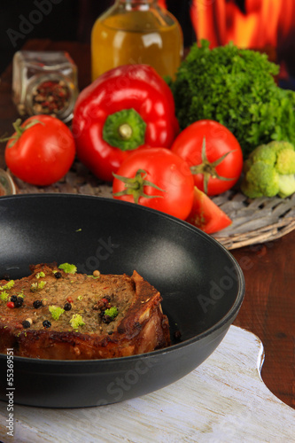 Piece of fried meat on pan on wooden table on fire background