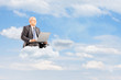 Mature businessman in suit flying on clouds with laptop outside