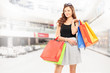 Satisfied woman posing with shopping bags in a shopping mall