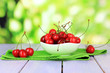 Cherry berries in bowl on wooden table on bright background