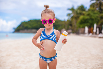 Little adorable girl in swimsuit rubs sunscreen herself