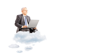 Mature businessman wearing suit and flying on clouds with laptop