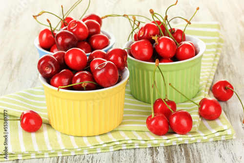 Cherry berries in bowls on wooden table close up