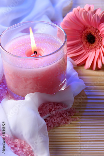 Beautiful candle with flower on white cloth, close up
