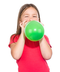 Little girl is inflating green balloon
