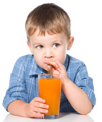 Little boy with glass of carrot juice