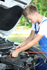 Young car mechanic uses battery jumper cables to charge dead