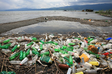 a pile of garbage and plastic bottles on the lake shore