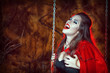 Screaming halloween woman in red cloak on the swing