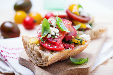 sandwich with red, yellow and black tomatoes and feta cheese