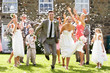 Guests Throwing Confetti Over Bride And Groom - 55374914