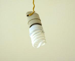 Energy saving bulb in white ceramic cartridge hangs close up
