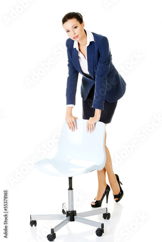 Beautiful successful businesswoman standing next to ofice chair