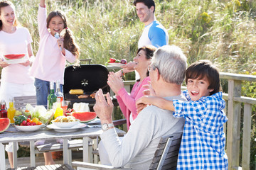 Multi Generation Family Having Outdoor Barbeque