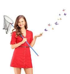 Smiling young female holding a butterfly net and butterflies aro