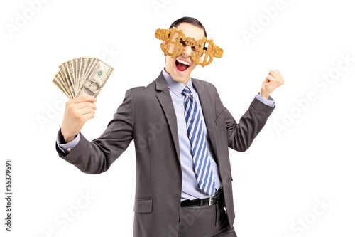 Smiling man wearing dollar sign glasses and holding dollars