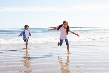 Children Running Away From Breaking Waves On Beach