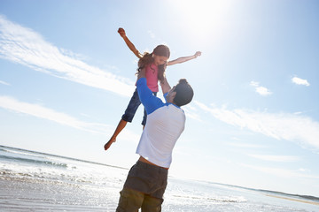 Father Throwing Daughter Into Air On Beach