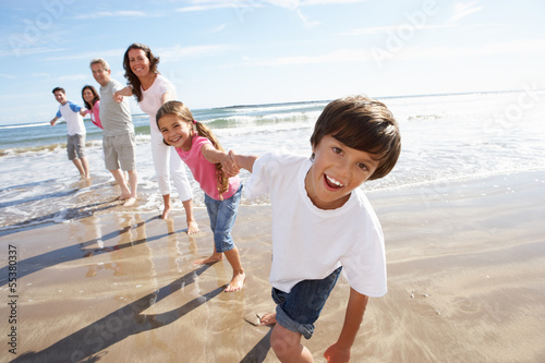 Multi Generation Family Having Fun On Beach Holiday
