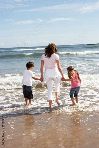 Mother And Children Having Fun On Beach Holiday