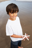 Boy Holding Starfish Found On Beach