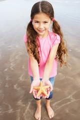 Girl Holding Starfish Found On Beach