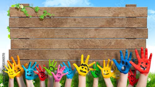 lanchende Kinderhände vor Holzschild